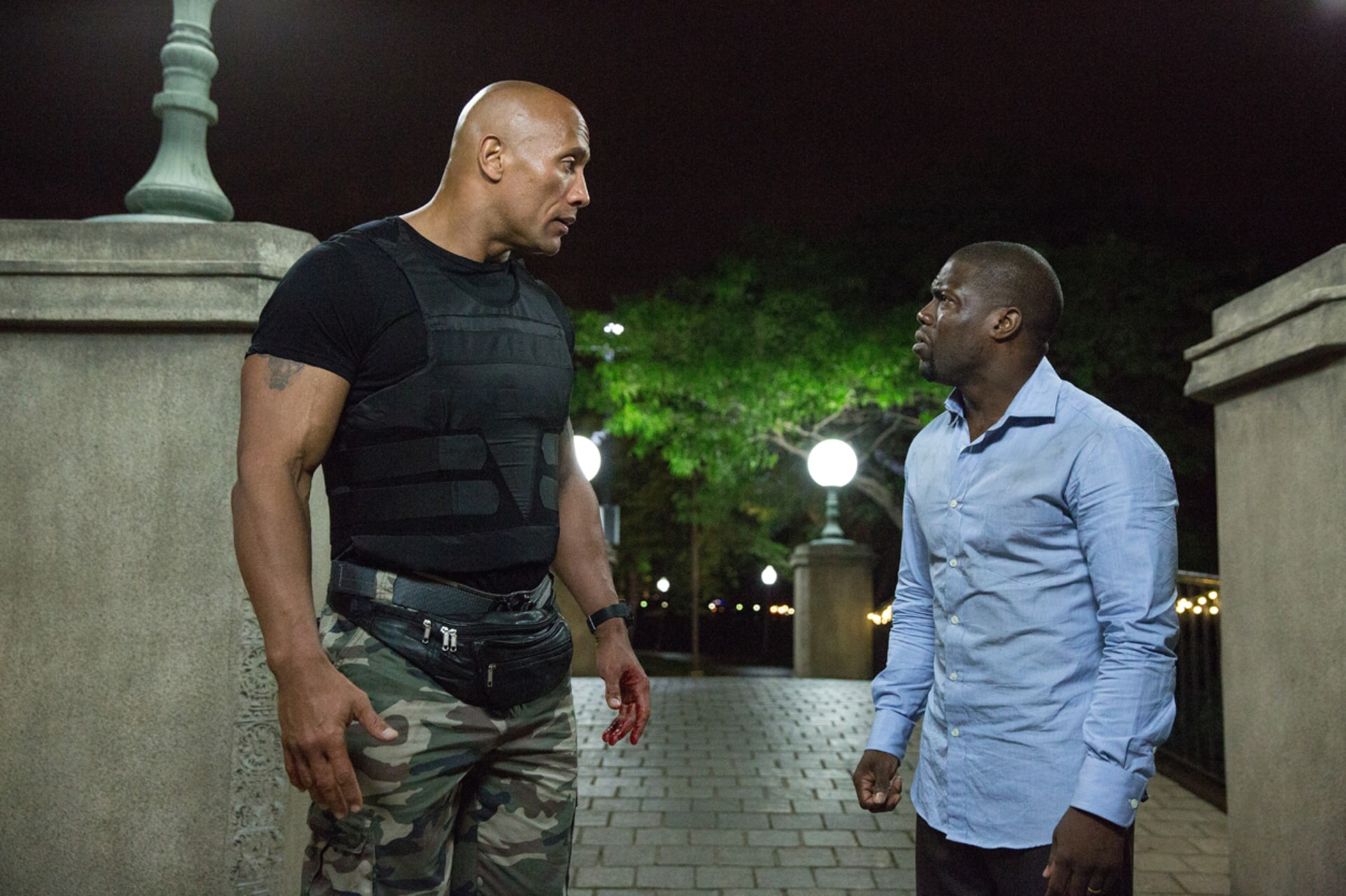 DWAYNE JOHNSON as Bob and KEVIN HART as Calvin standing on a bridge in a park at night