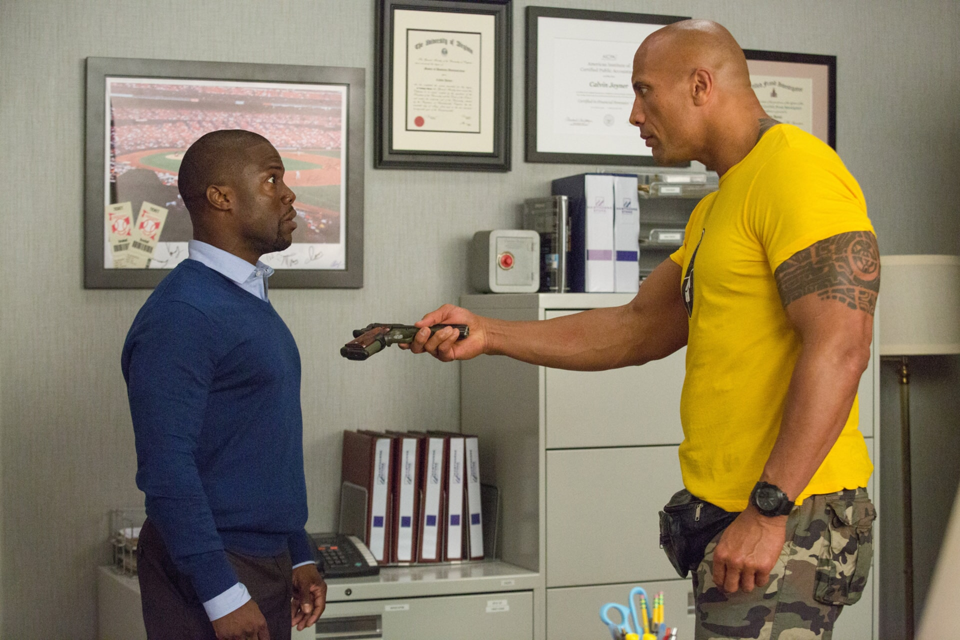 KEVIN HART as Calvin and DWAYNE JOHNSON as Bob handing over a gun