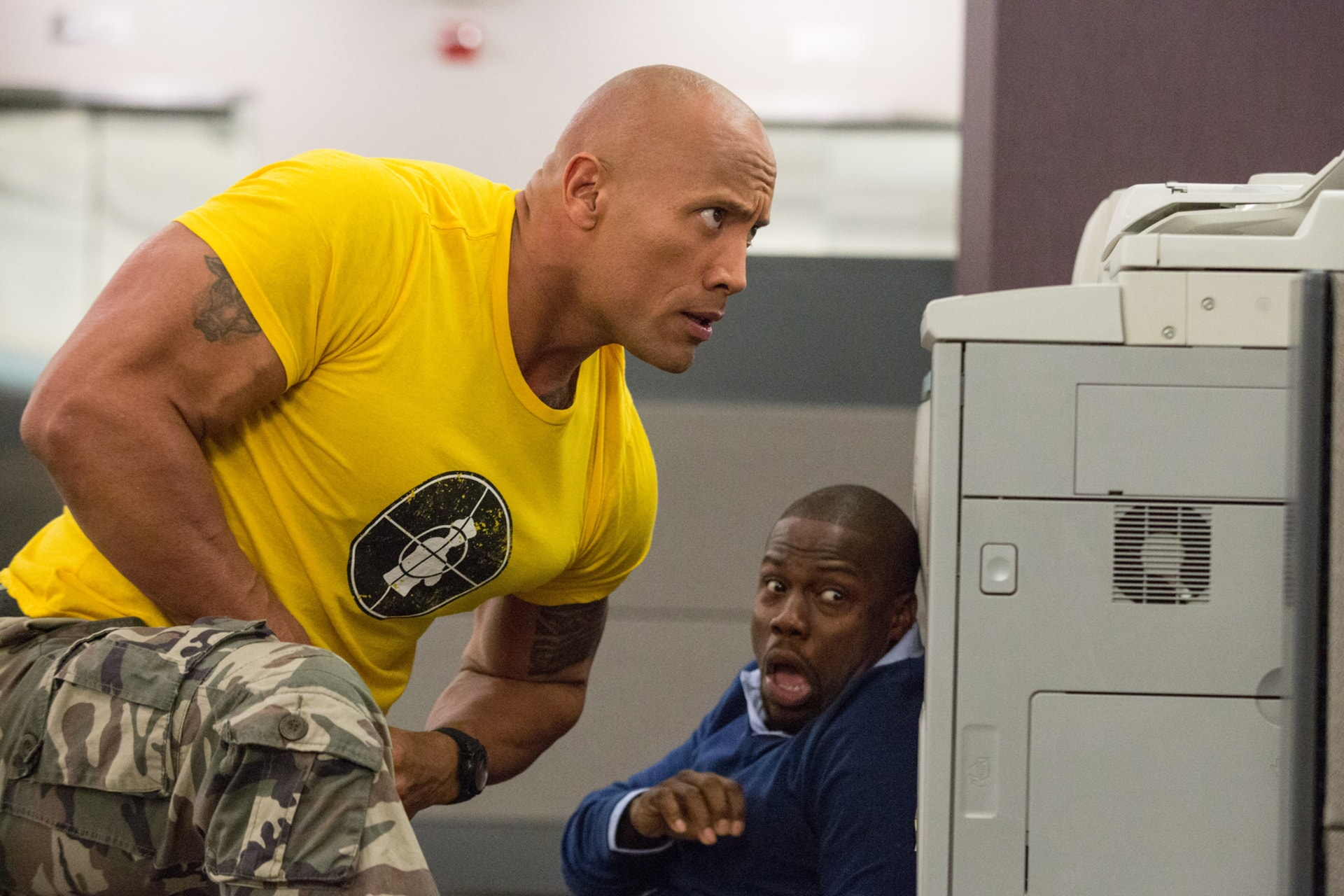 KEVIN HART as Calvin and DWAYNE JOHNSON as Bob crouching down behind office equipment
