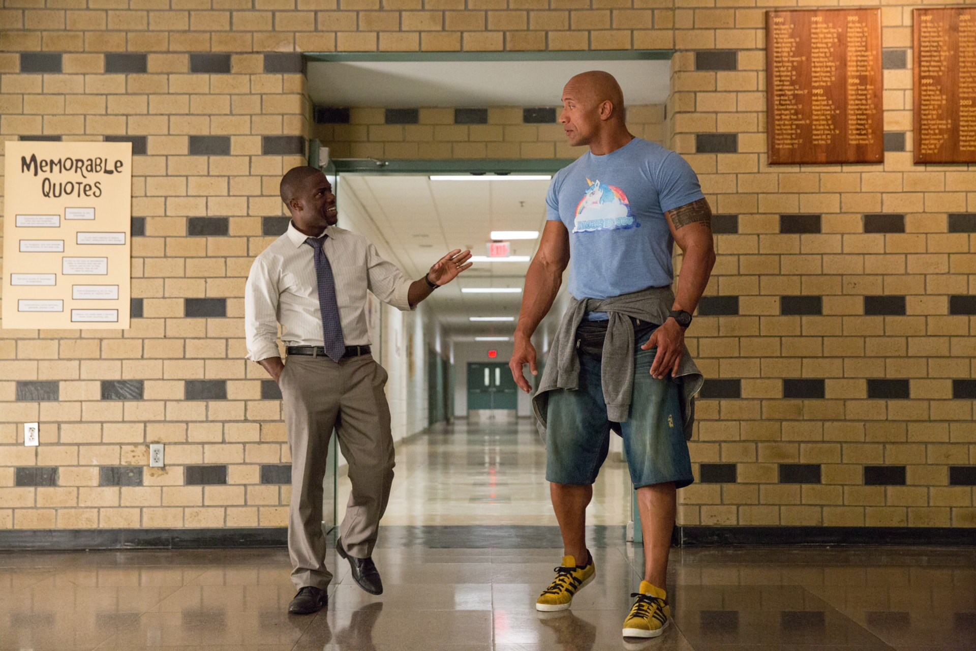 KEVIN HART as Calvin and DWAYNE JOHNSON as Bob in a high school hallway