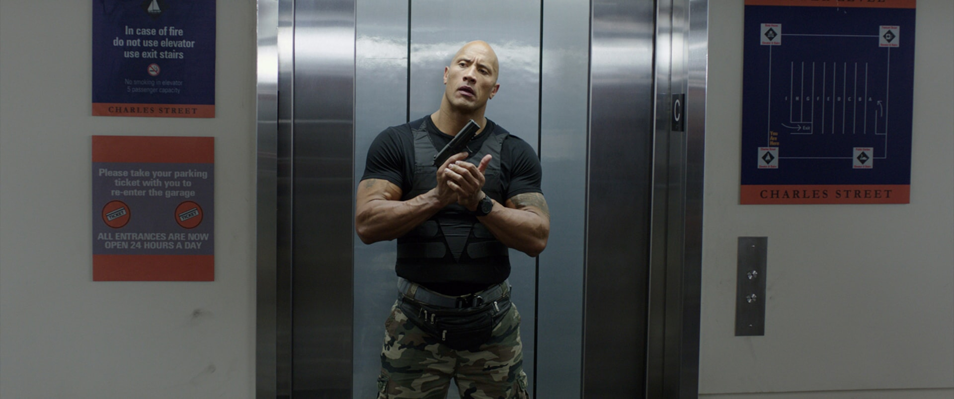 DWAYNE JOHNSON as Bob holding a gun in an elevator