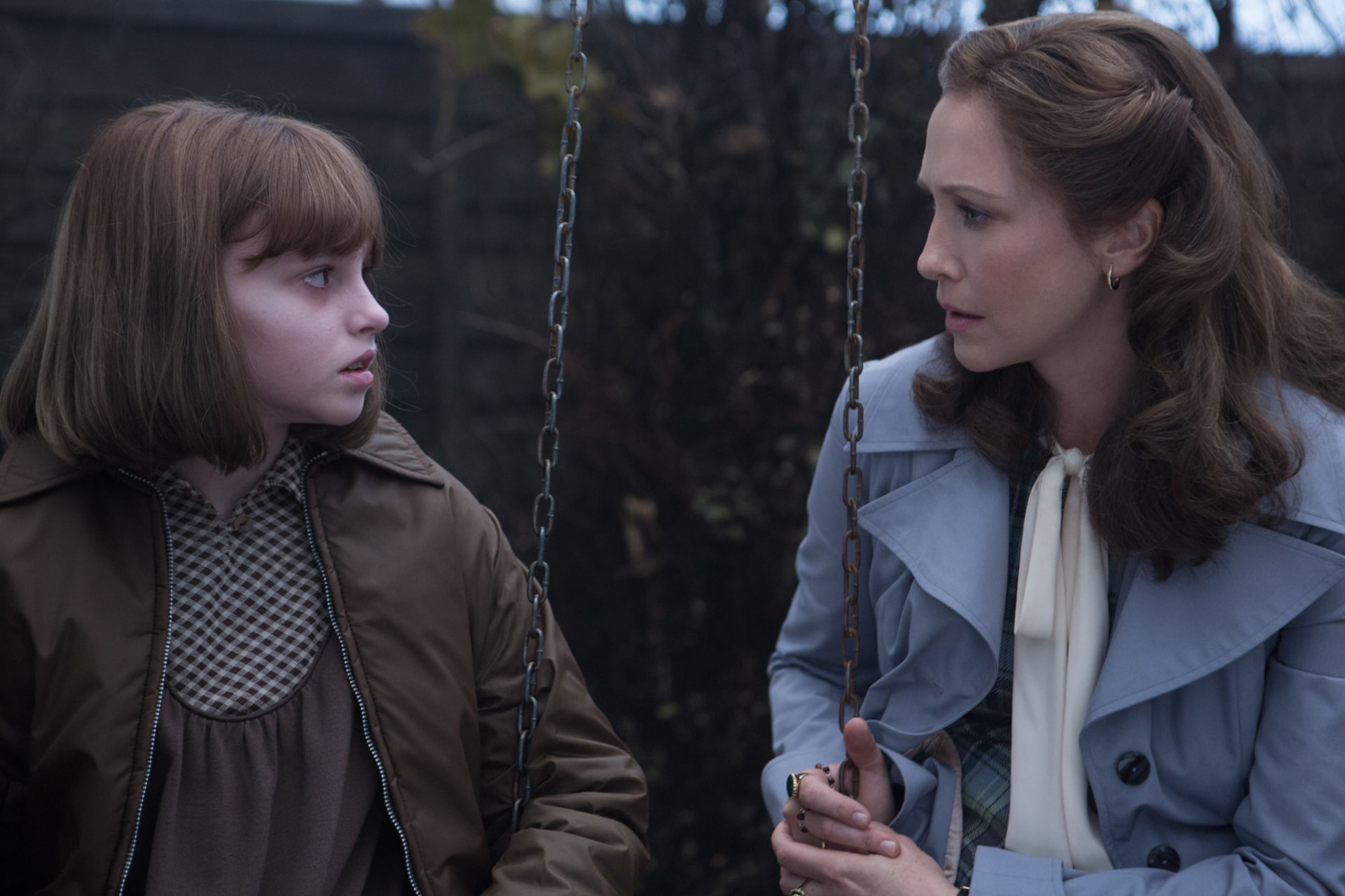 Janet Hodgson and VERA FARMIGA as Lorraine Warren looking at each other on a swing set