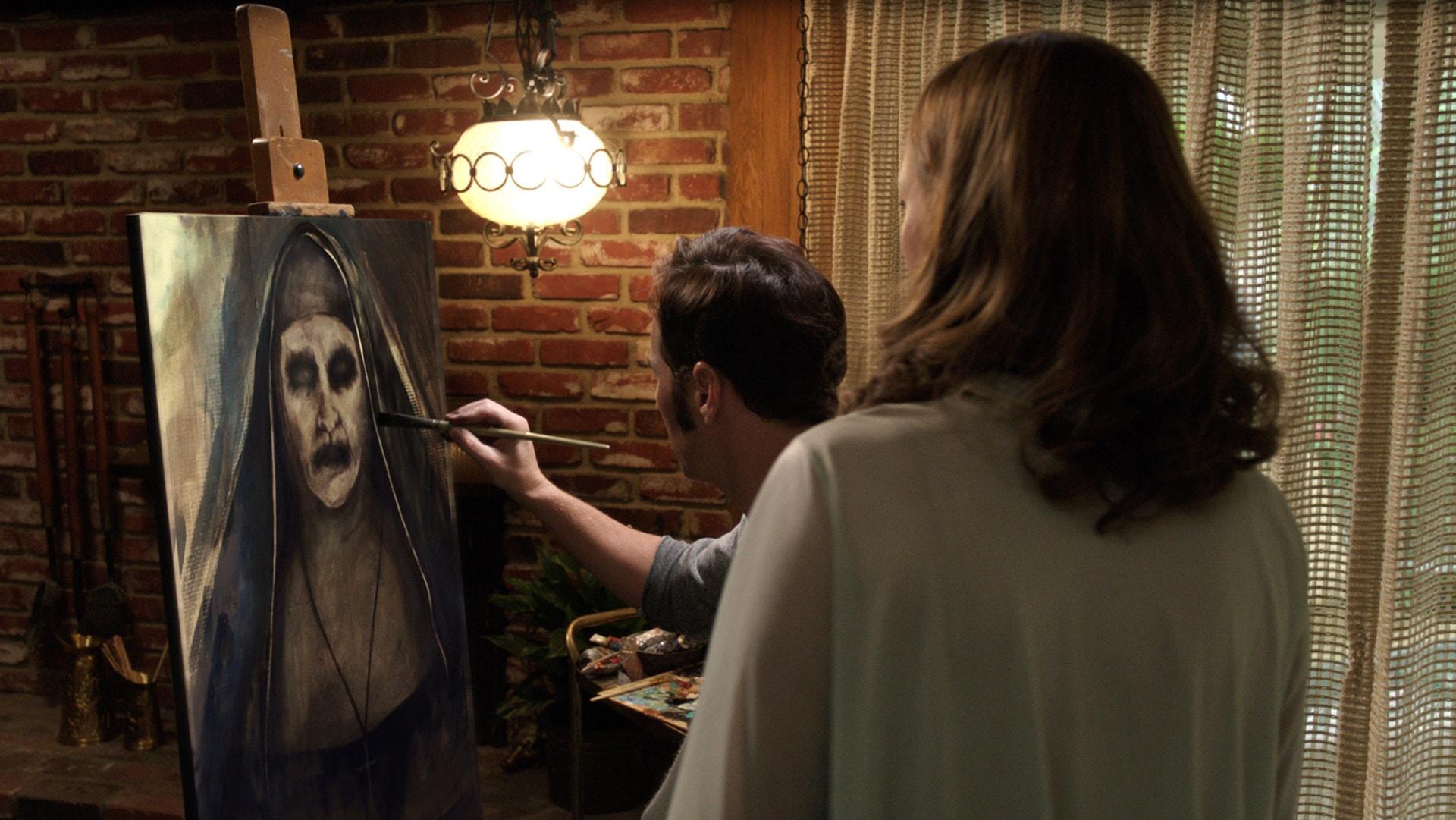 PATRICK WILSON as Ed Warren painting a portrait of a ghostly nun while VERA FARMIGA as Lorraine Warren looks on behind him