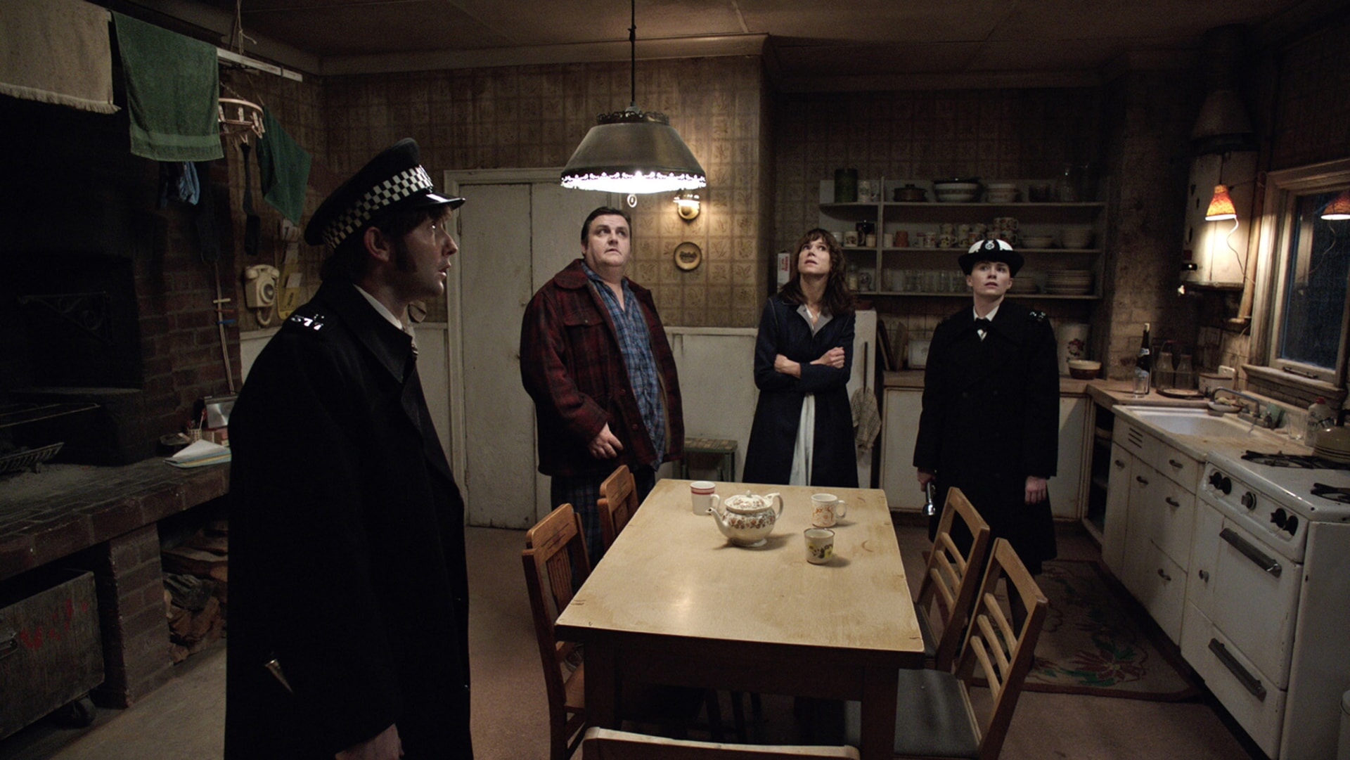 SIMON DELANEY as Vic Nottingham and FRANCES O'CONNOR as Peggy Hodgson standing in a kitchen looking up at the ceiling