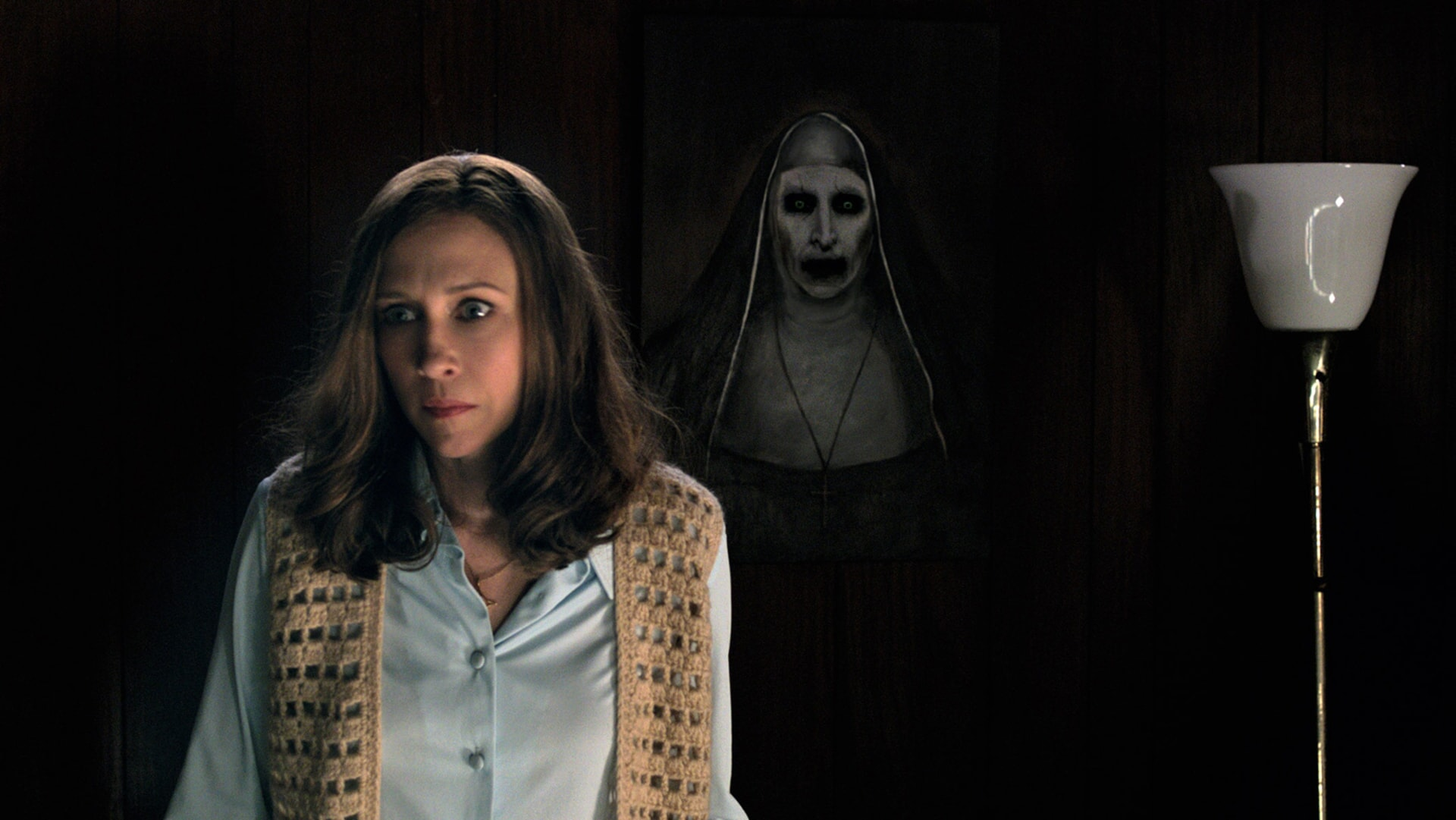 VERA FARMIGA as Lorraine Warren wearing a crocheted sweater vest with a ghostly apparition appearing over her shoulder