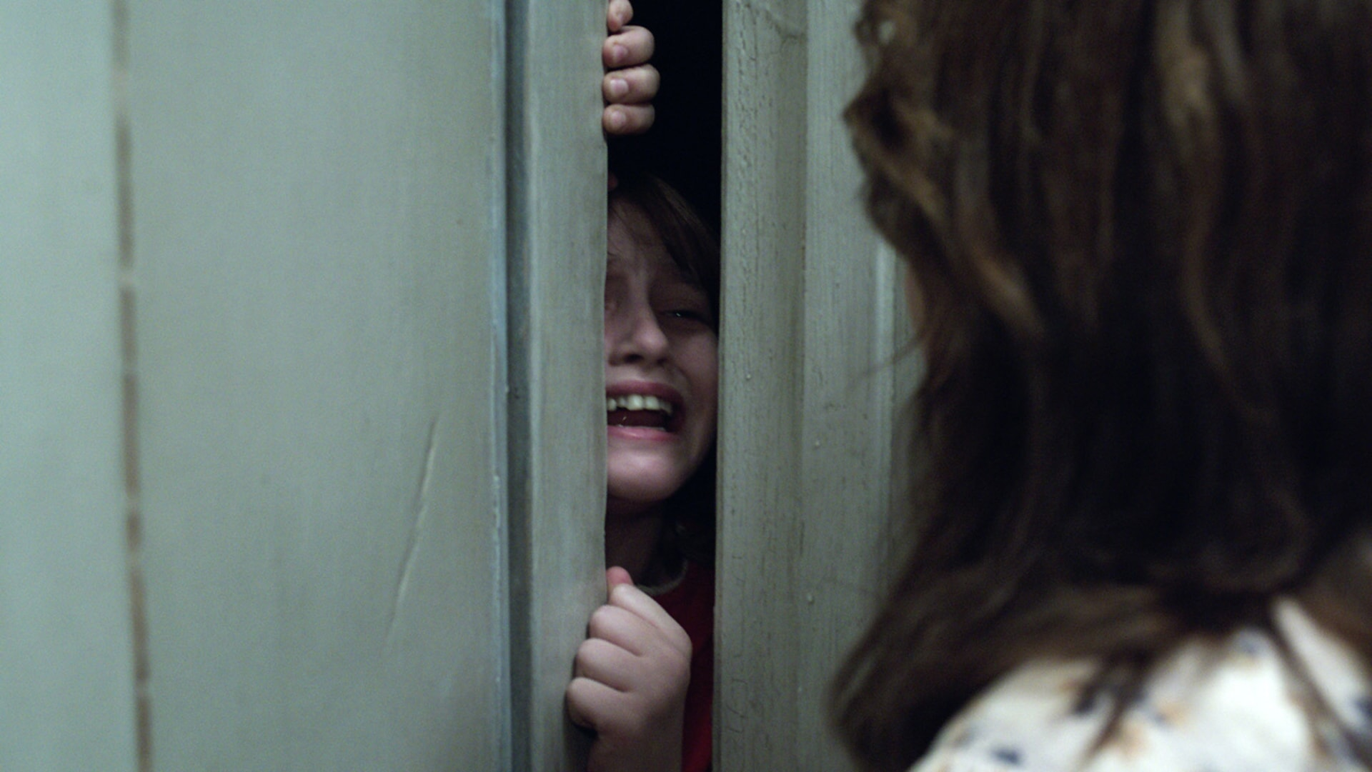 MADISON WOLFE as Janet Hodgson crying out through a crack in a door