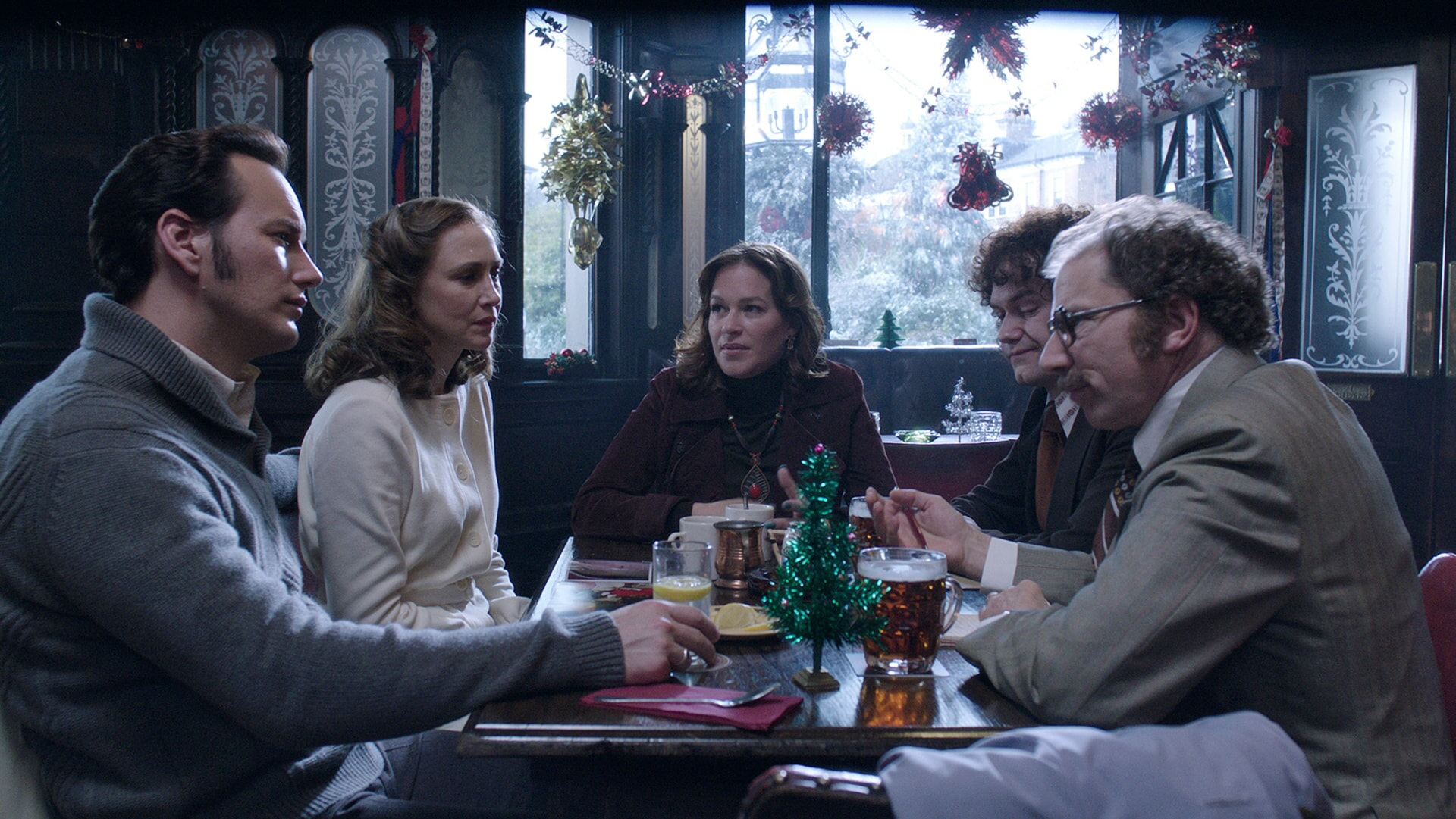 PATRICK WILSON as Ed Warren, VERA FARMIGA as Lorraine Warren, FRANKA POTENTE as Anita Gregory and SIMON McBURNEY as Maurice Grosse meeting in a restaurant decorated with Christmas ornaments
