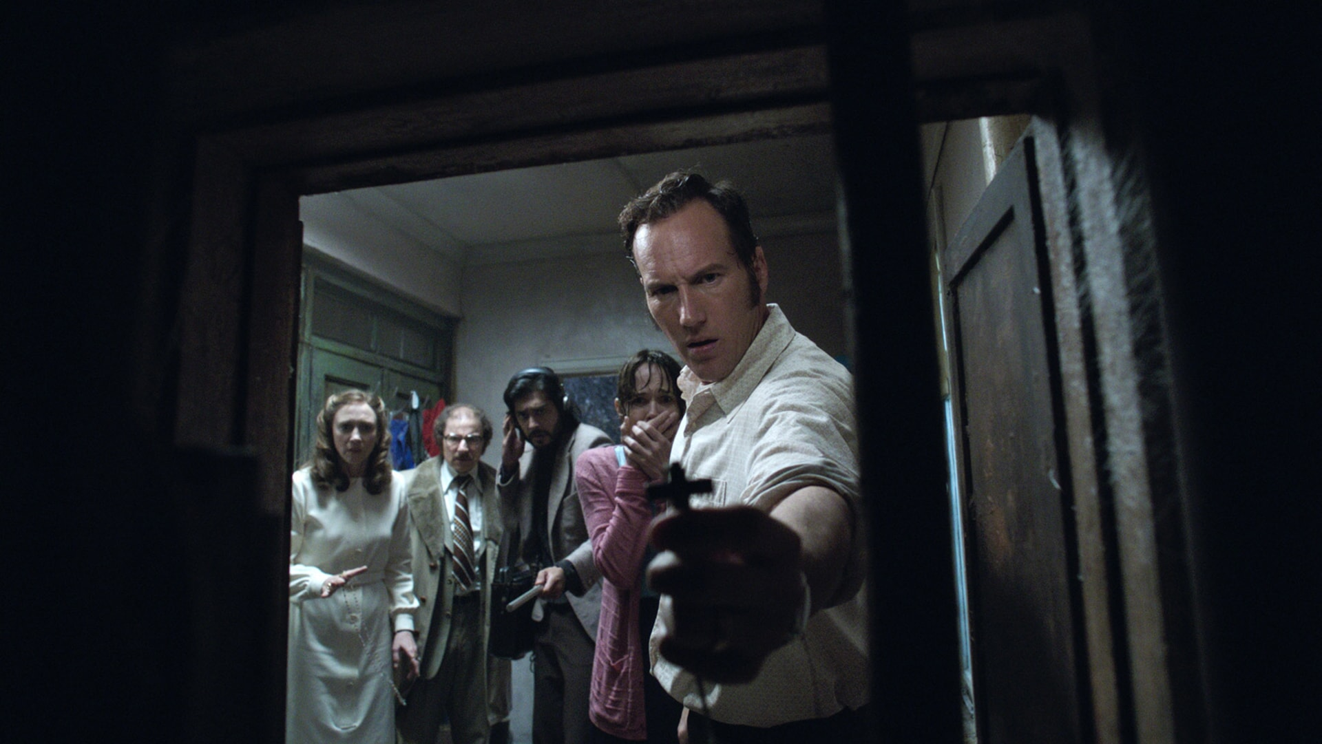 VERA FARMIGA as Lorraine Warren, SIMON McBURNEY as Maurice Grosse, ABHI SINHA as Harry Whitmark, FRANCES O'CONNOR as Peggy Hodgson and PATRICK WILSON as Ed Warren, who is holding up a crucifix