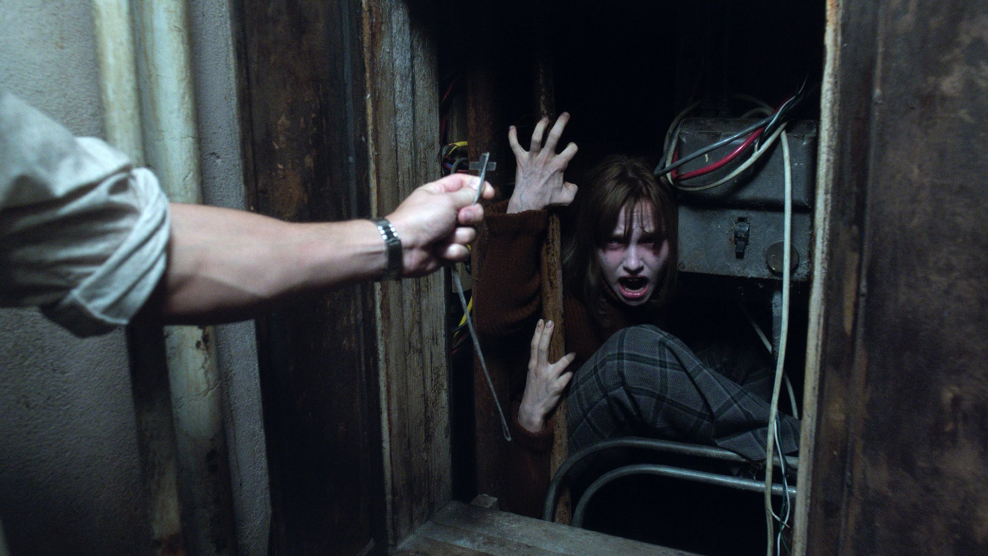 MADISON WOLFE as Janet Hodgson crouching in fear from a crucifix