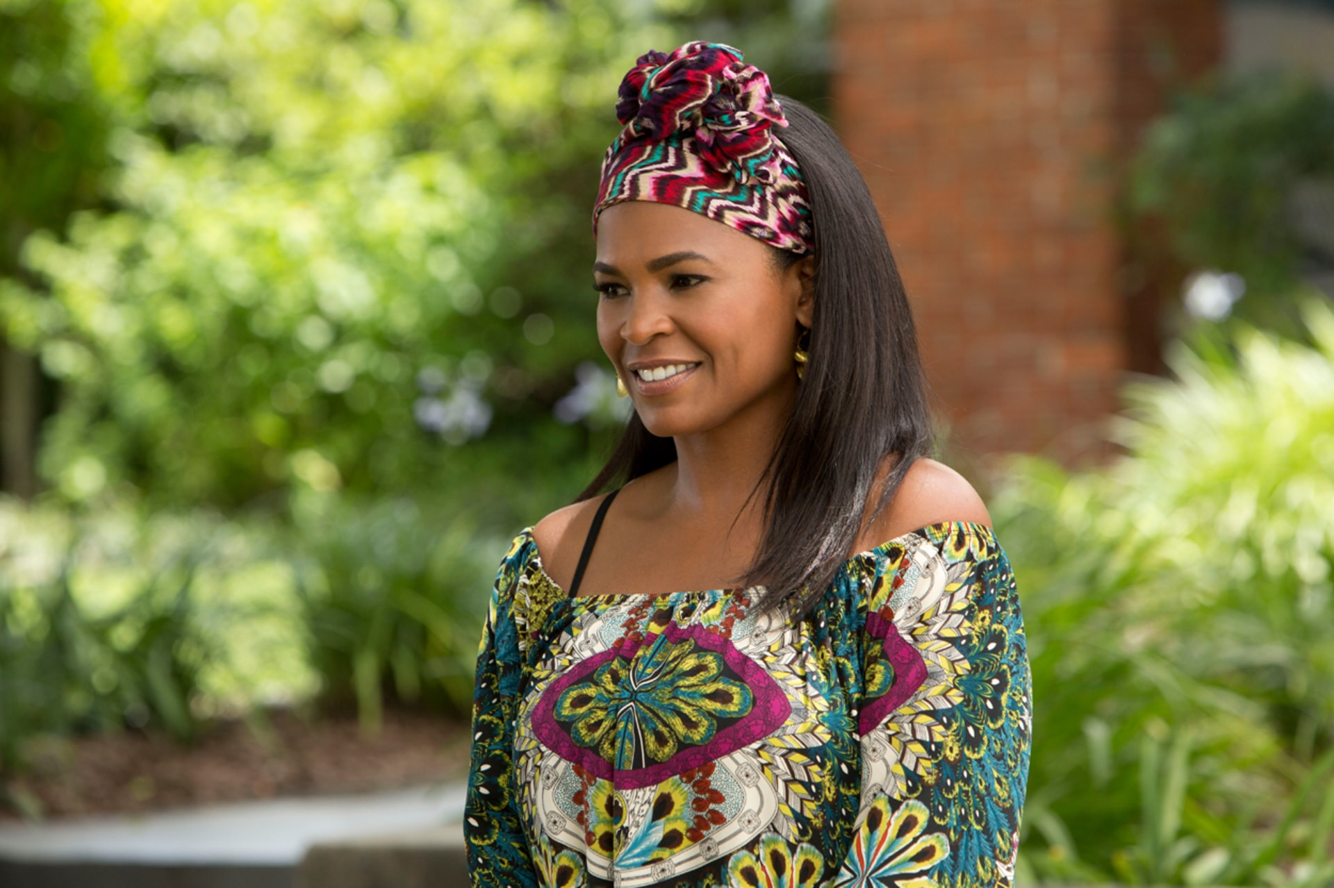 NIA LONG as Hannah wearing a printed headscarf and top
