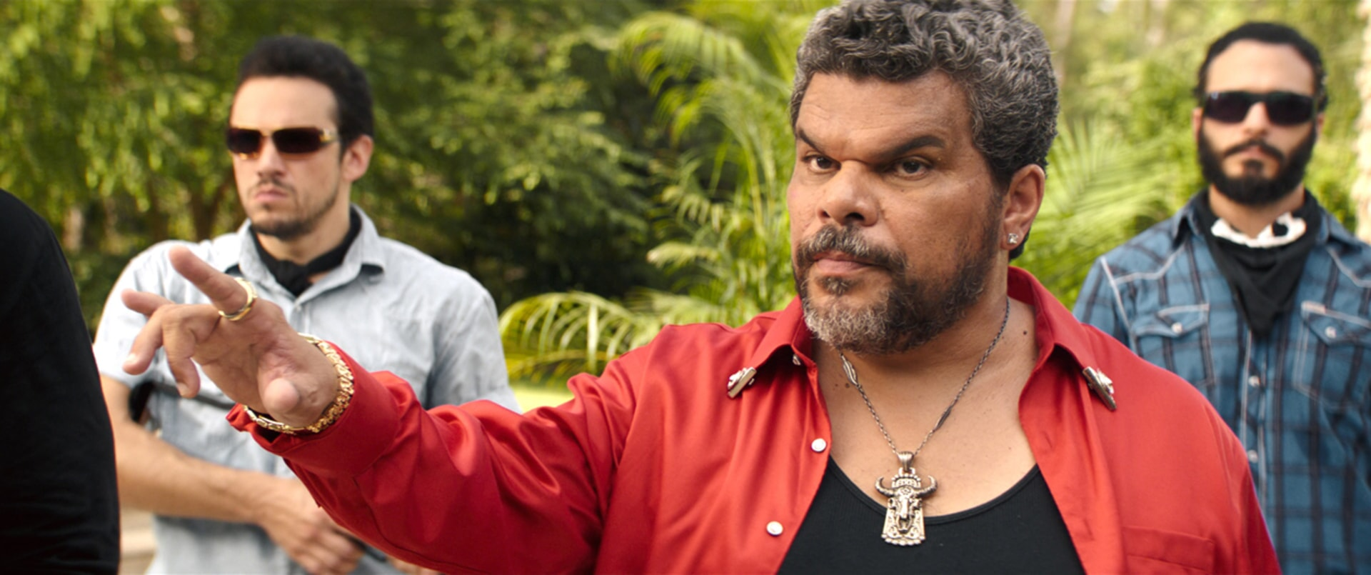 LUIS GUZMÁN as Bacon wearing a red jacket and amulet necklace