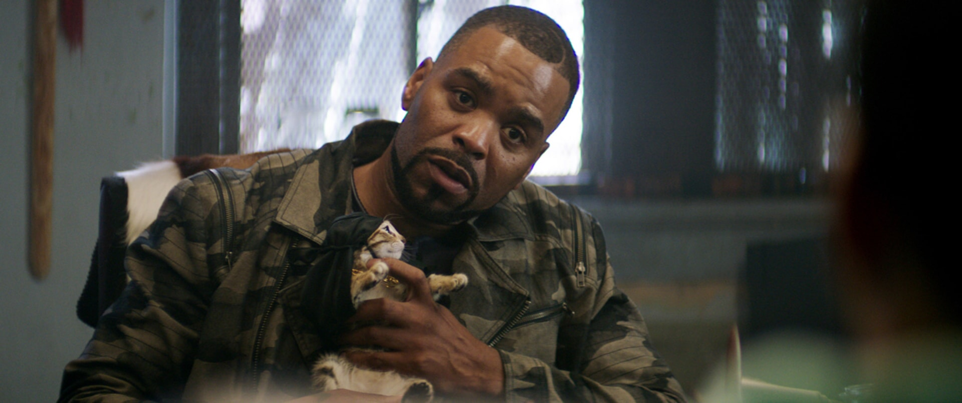 METHOD MAN as Cheddar holding Keanu the kitten who is wearing a black headwrap and gold chain