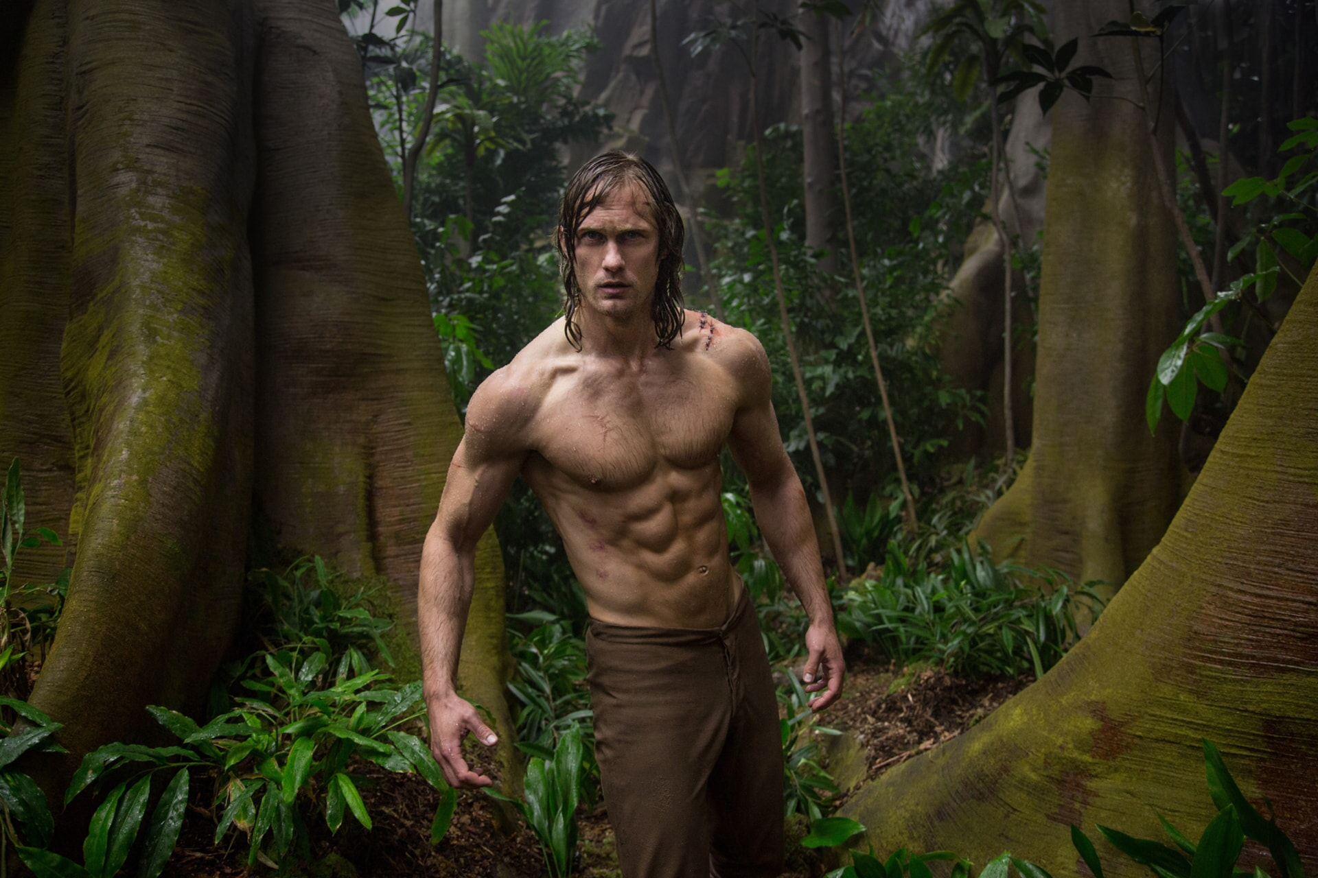Shirtless Alexander Skarsgård as Tarzan standing in the jungle