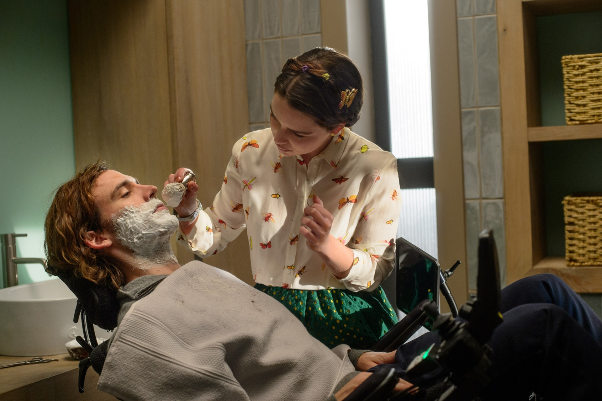SAM CLAFLIN as Will Traynor lying back in wheelchair and EMILIA CLARKE as Lou Clark shaving his face.