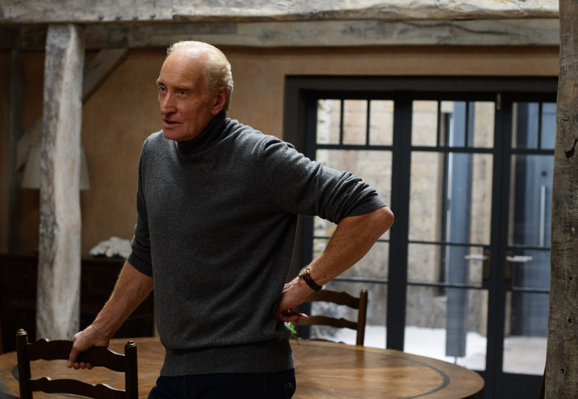 CHARLES DANCE as Stephen Traynor wearing a dark turtleneck with his hand on his hip, standing by a table.