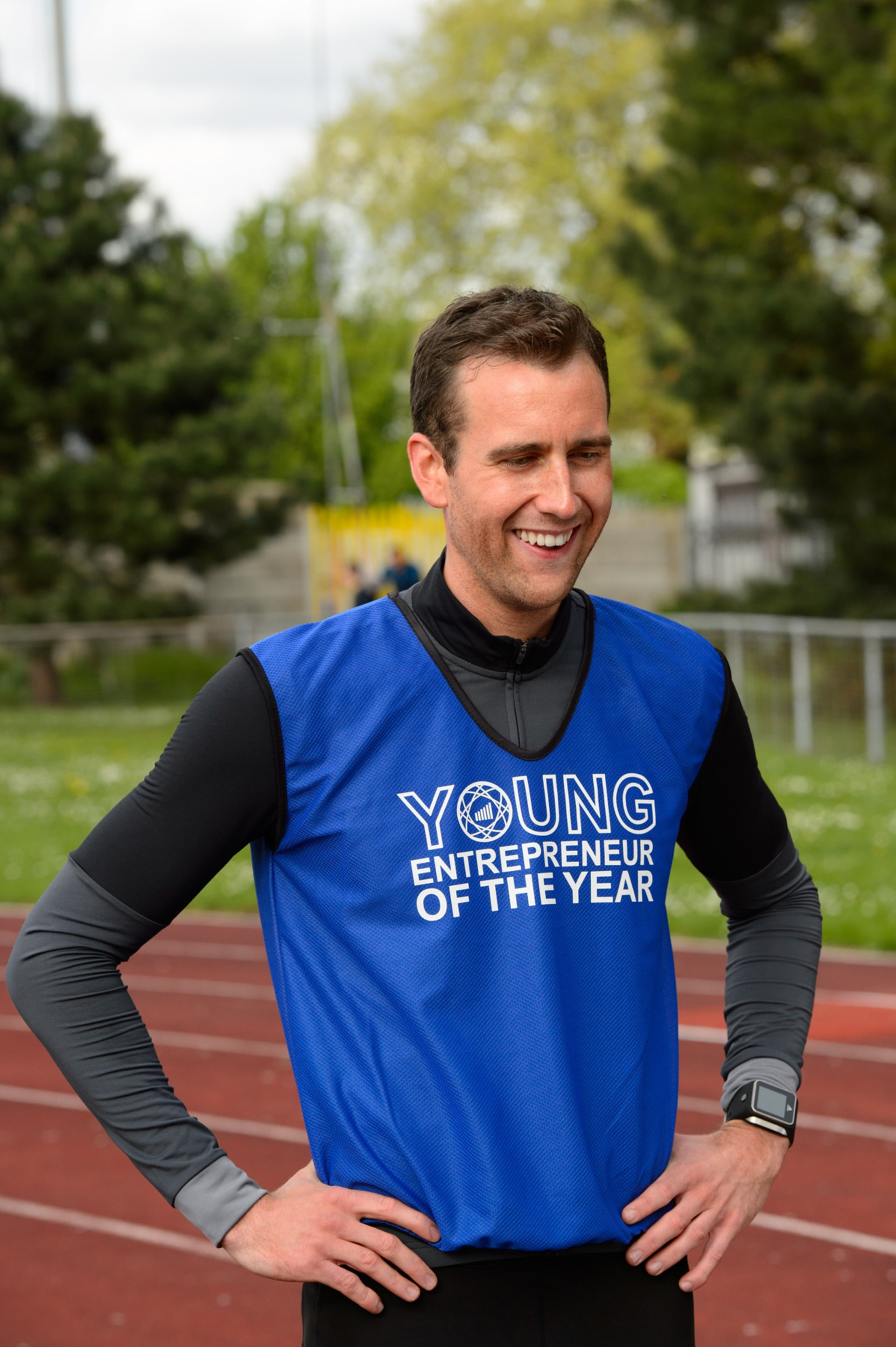 MATTHEW LEWIS as Patrick on a race track wearing a running shirt that says Young Entrepreneur of The Year.