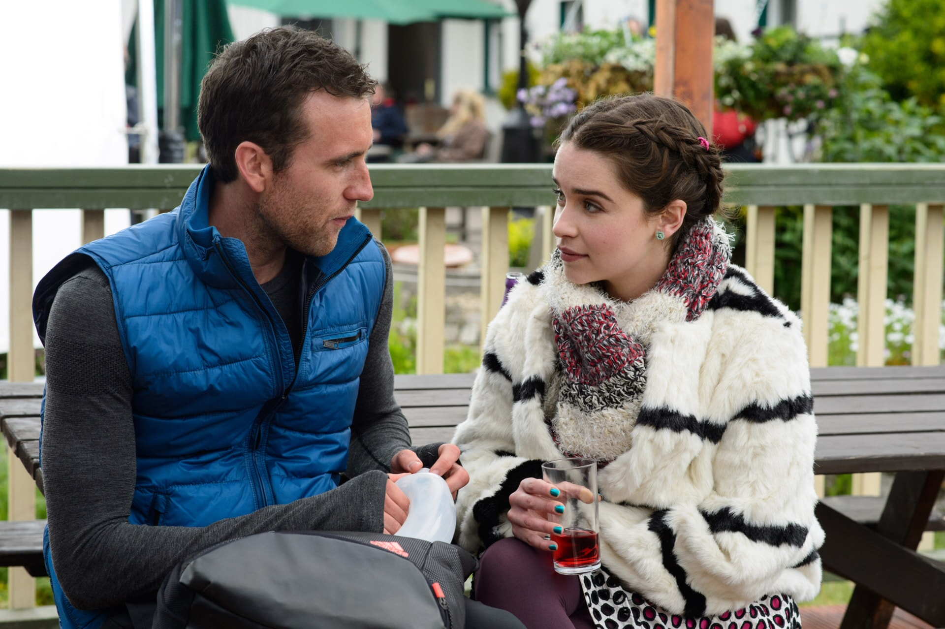 MATTHEW LEWIS as Patrick and EMILIA CLARKE as Lou Clark sitting and talking outdoors.