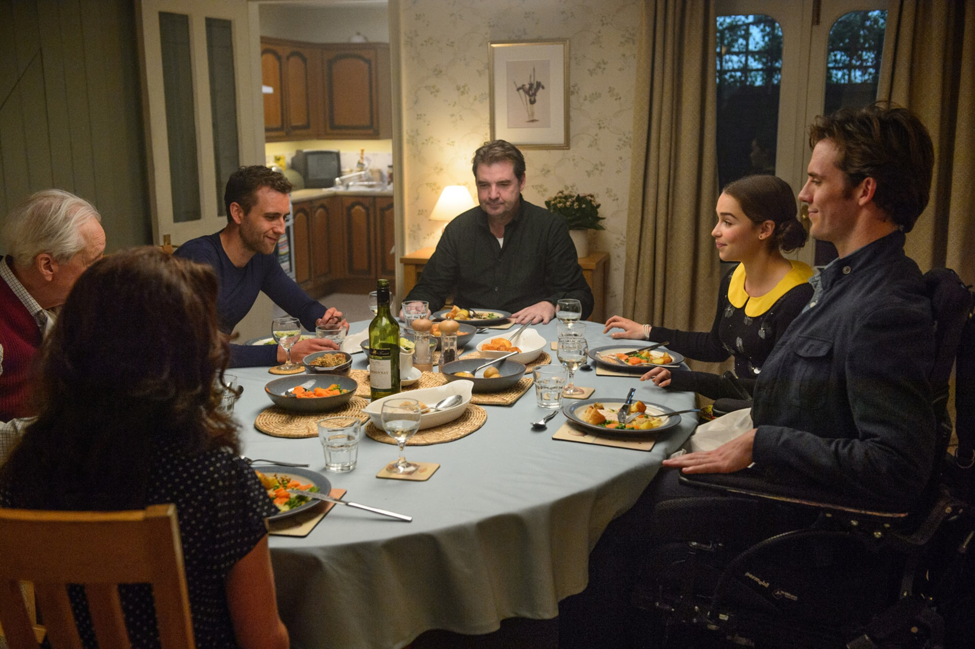 SAM CLAFLIN as Will Traynor, EMILIA CLARKE as Lou Clark, BRENDAN COYLE as Bernard Clark and MATTHEW LEWIS as Patrick sitting at a family-style dinner.