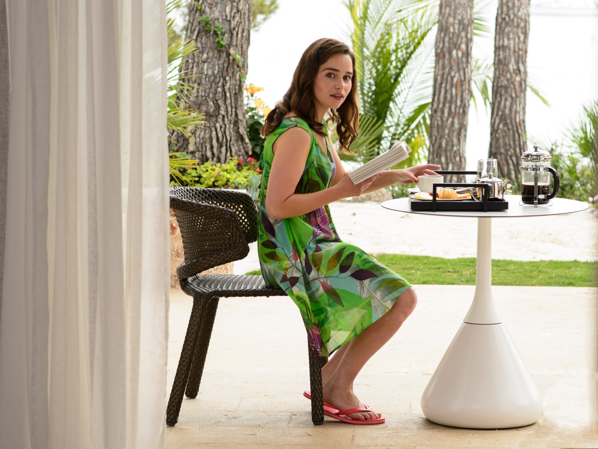 EMILIA CLARKE as Lou Clark eating breakfast outdoors in a tropical setting.