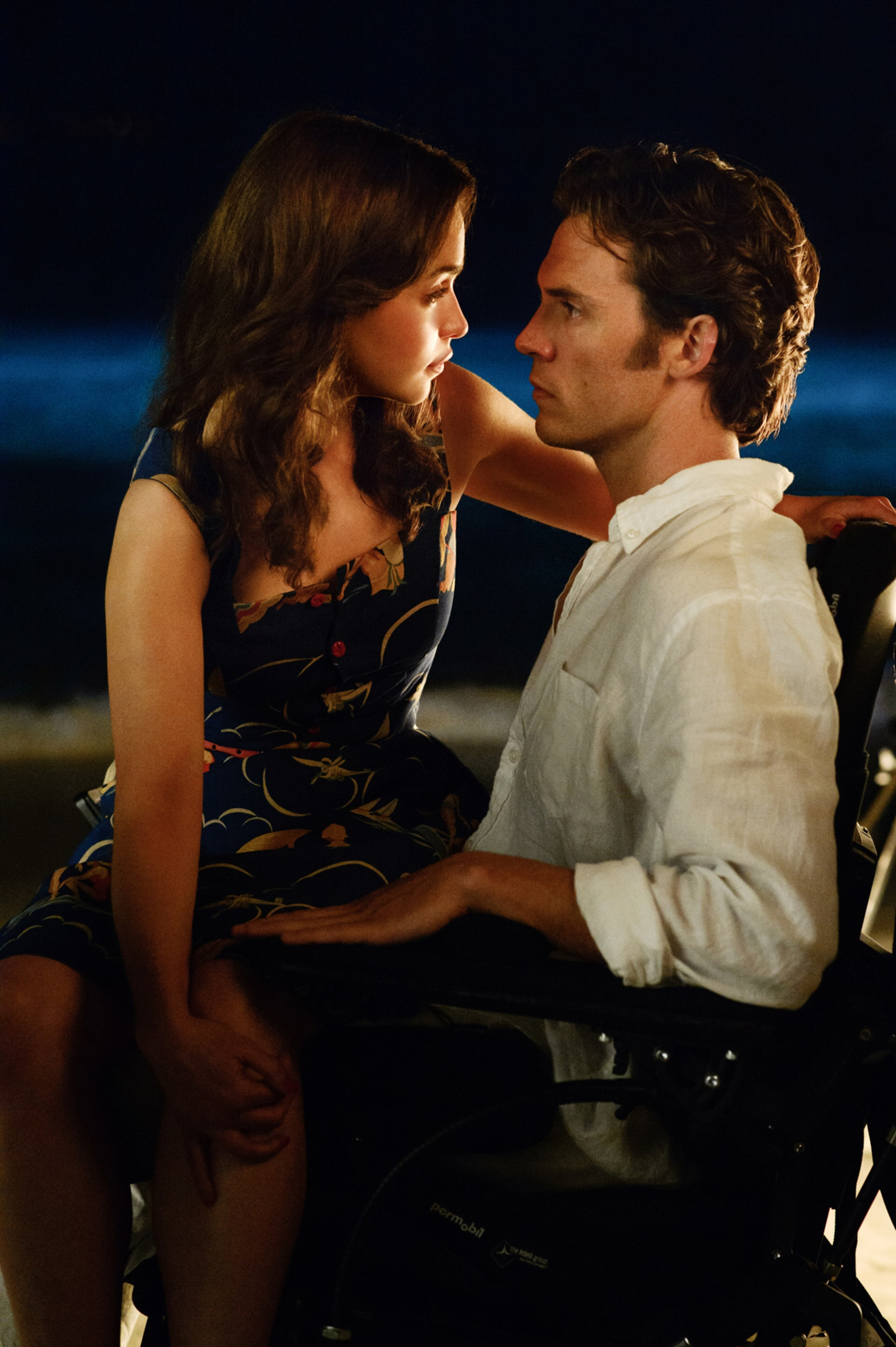 EMILIA CLARKE as Lou Clark sitting on the lap of SAM CLAFLIN as Will Traynor on a beach at nighttime.