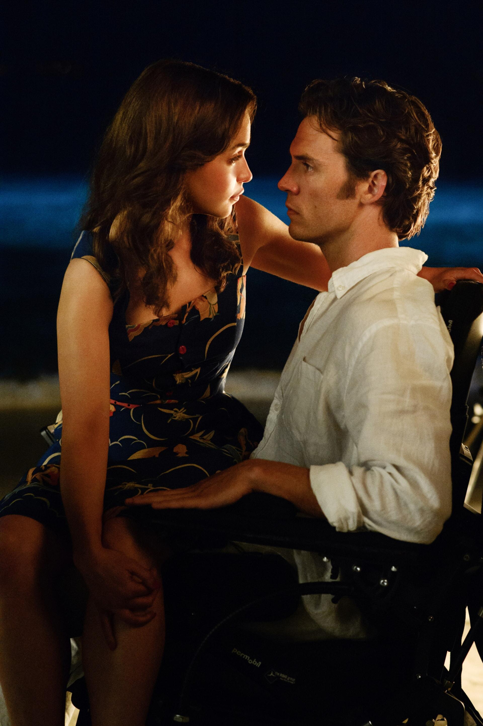 EMILIA CLARKE as Lou Clark sitting on the lap of SAM CLAFLIN as Will Traynor on a beach at nighttime.