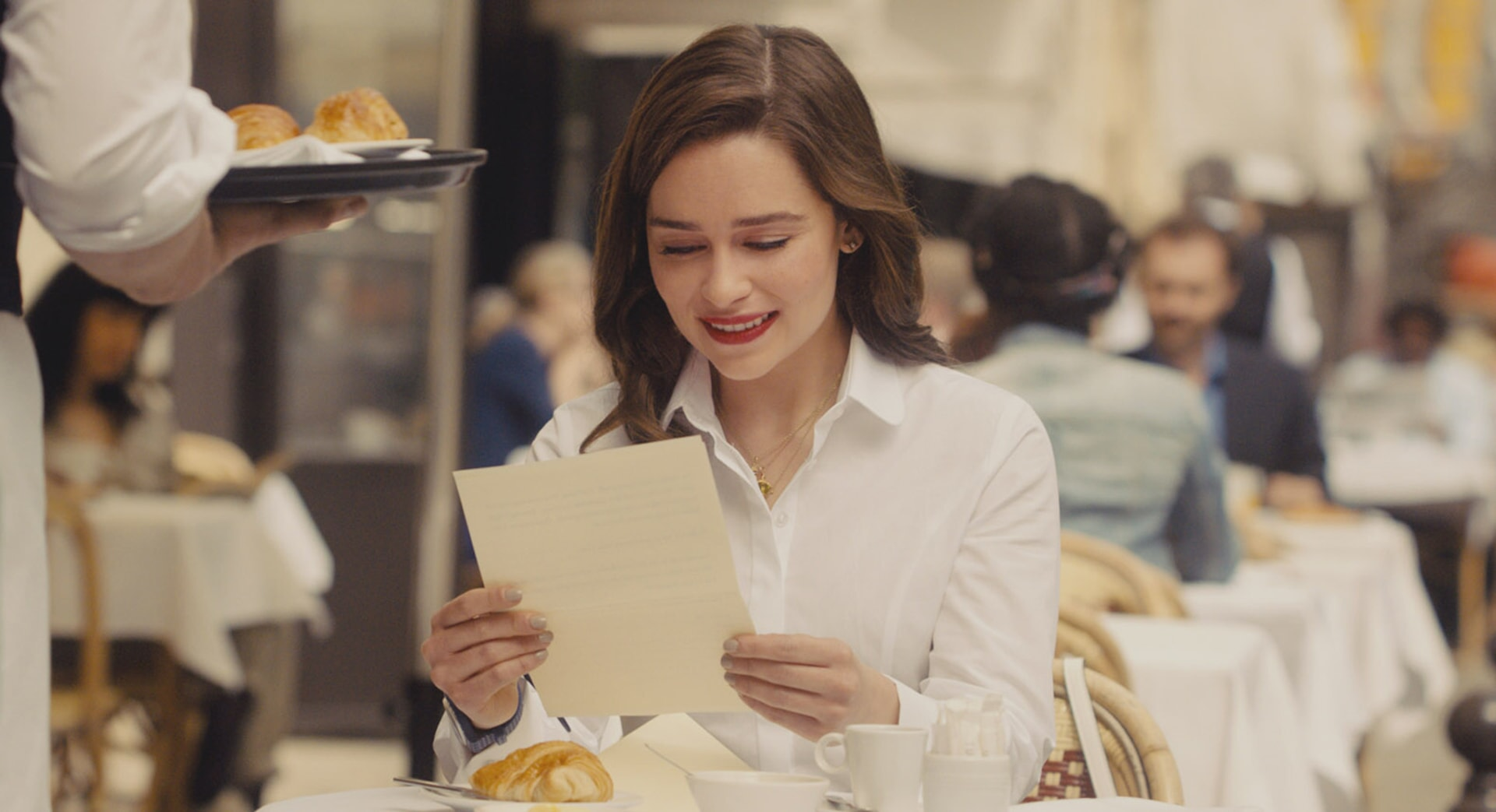 EMILIA CLARKE as Lou Clark reading a note while at an outdoor cafe.