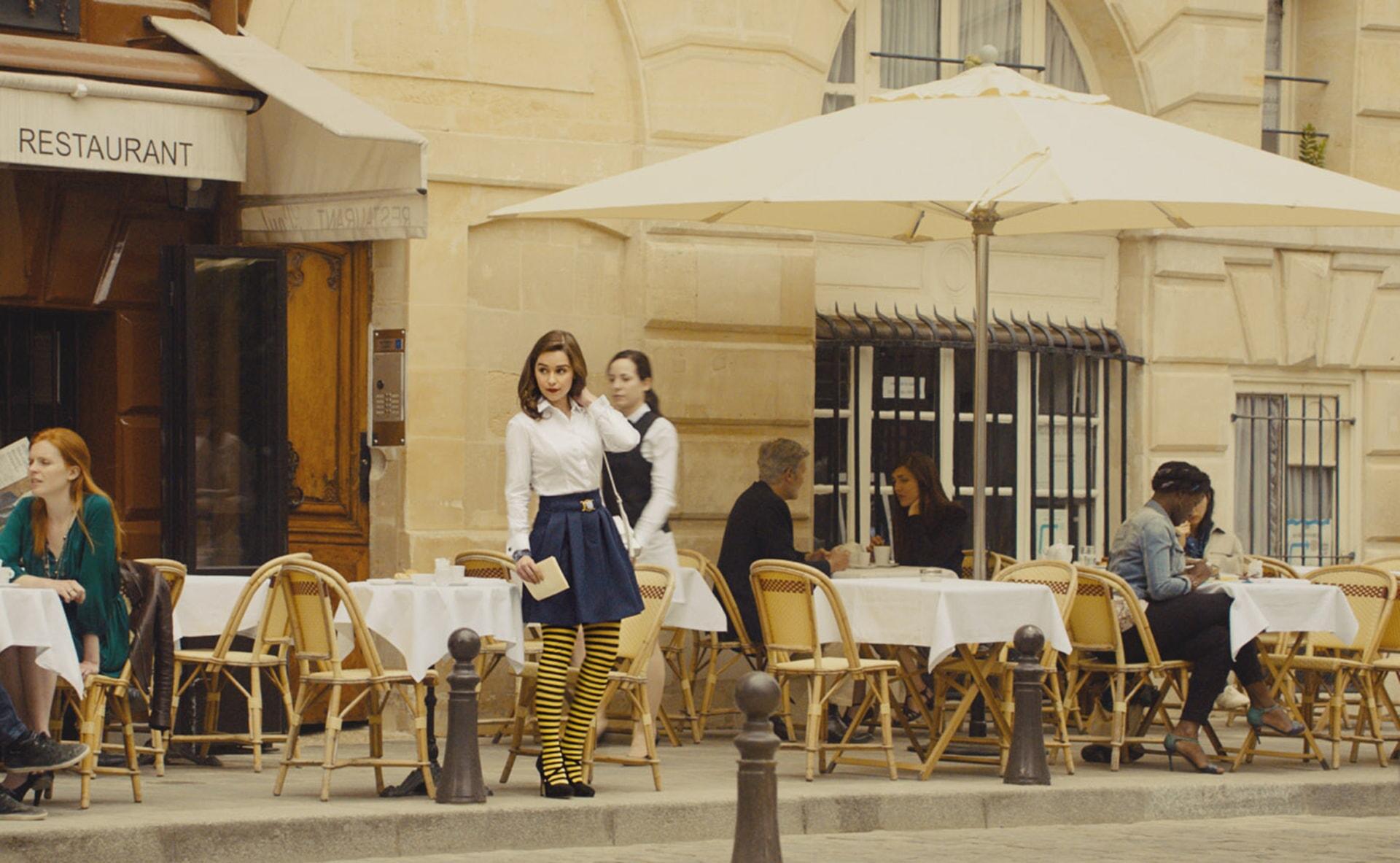 EMILIA CLARKE as Lou Clark standing outside an outdoor cafe.