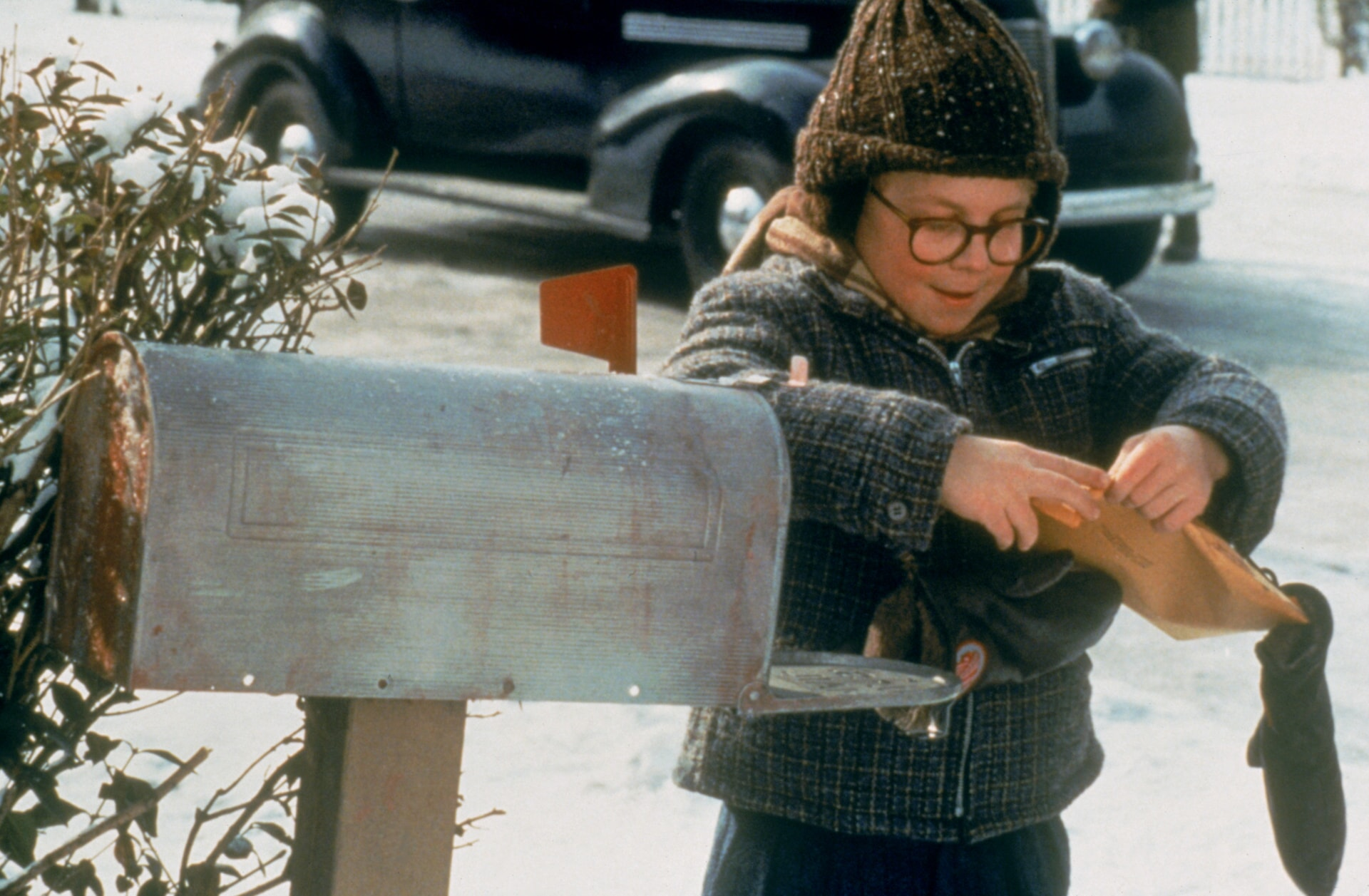 Ralphie opening a package at the mailbox