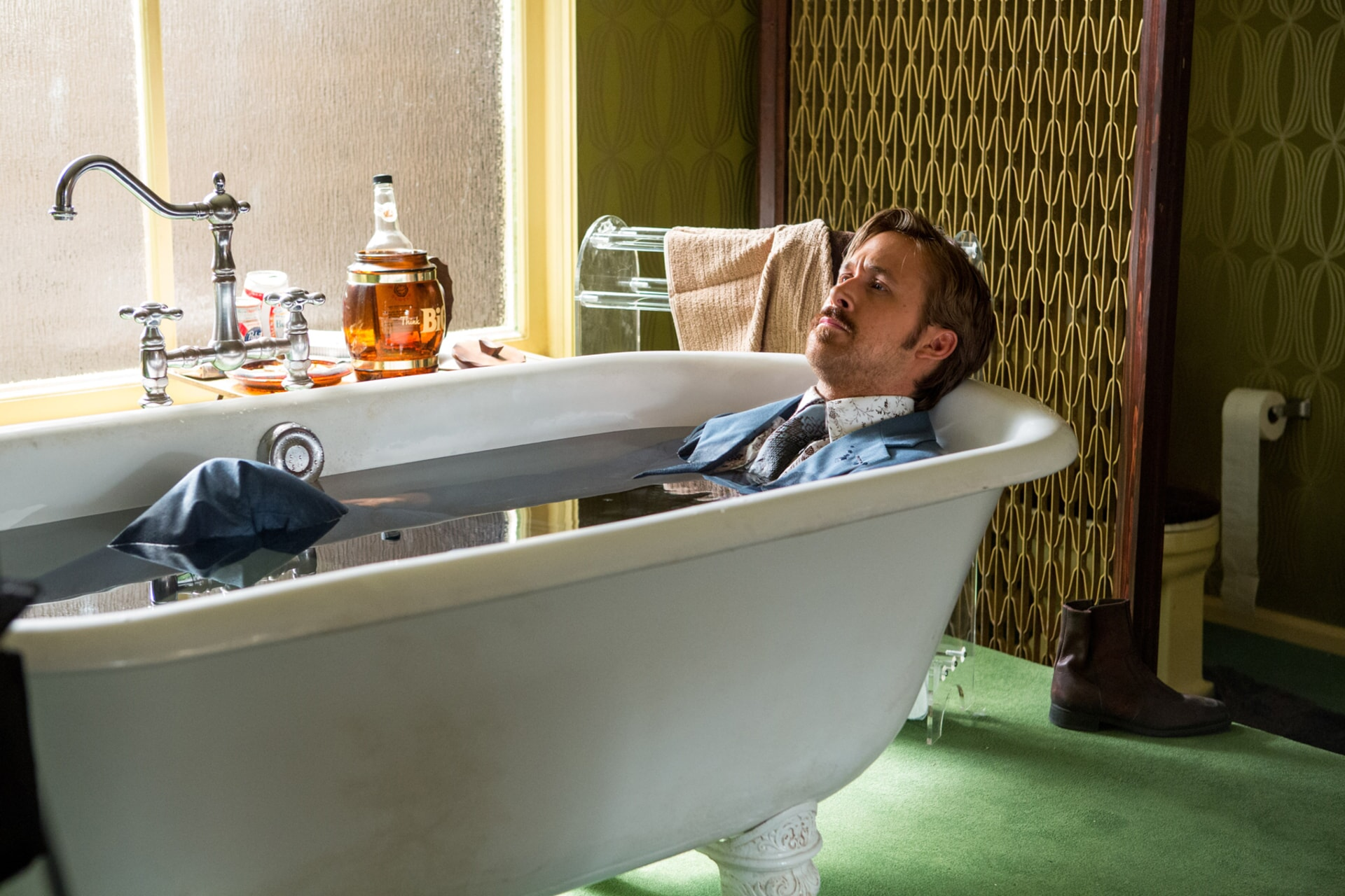 RYAN GOSLING as Holland March, wearing a blue 1970s suit, lying a bathtub