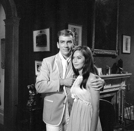 Medium shot of John Fraser as Richard Poole embracing Nancy Kwan as Tamahine.