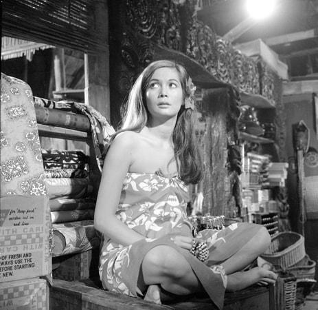 Medium shot of Nancy Kwan as Tamahine wearing flowers in hair