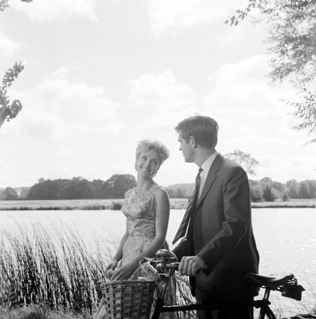 Medium shot of John Fraser as Richard Poole, pushing bicycle, walking alongside lake with Justine Lord as Diana.