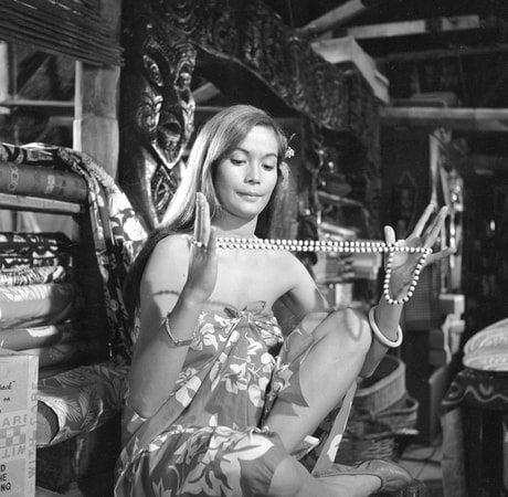 Medium shot of Nancy Kwan as Tamahine wearing dress/pareu and looking at necklace she holds in hand.