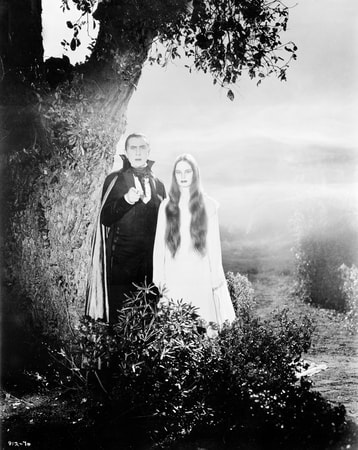 Full shot of Bela Lugosi as Count Mora and Carroll Borland as Luna Mora both standing by a tree.