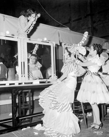 Full shot of chorus girl sitting down at make-up table, wearing elaborate dance costume, with woman taking her picture from above.