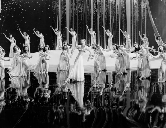 Wide shot of Eleanor Powell as Clare Bennett, dancing in front of chorus girls during musical number.