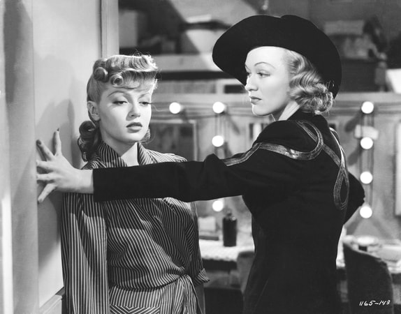 Medium shot of Lana Turner as Sheila 'Red' Regan leaning against wall and Eve Arden as Patsy Dixon with hat blocking her with hand on wall