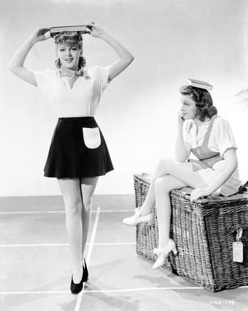 Full shot of Lana Turner as Sheila 'Red' Regan standing with book on head being held by both hands and Judy Garland as Susan Gallagher sitting on trunk with book on head, legs crossed and chin resting on fist