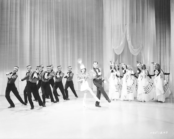 Wide angle shot of Judy Garland as Susan Gallagher with hat and baton performing on stage with unknown dancers