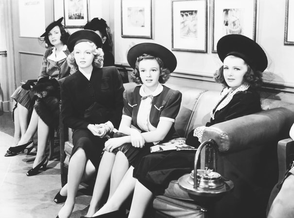 Wide angle shot of Lana Turner as Sheila 'Red' Regan with hat sitting on couch next to Judy Garland as Susan Gallagher