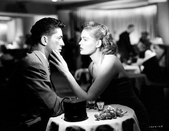 Medium profile shot of Farley Granger as Joe Norson seated at nightclub table with Jean Hagen as Harriette Sinton.