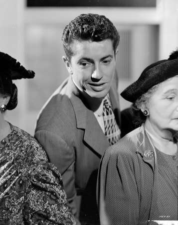 Medium shot of Farley Granger as Joe Norson leaning in between two women.