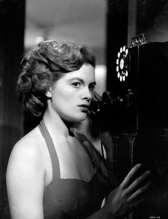 Medium shot of Jean Hagen as Harriette Sinton using pay phone.