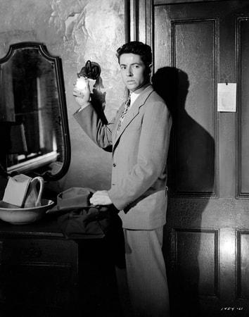 Medium shot of Farley Granger as Joe Norson adjussting a light bulb