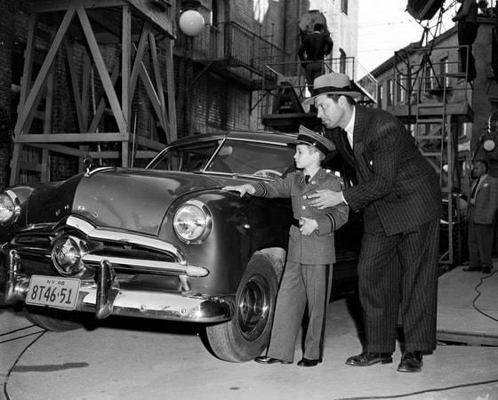 Behind-the_scenes shot of James Craig as George Garsell, wearing hat, and young boy standing next to car.