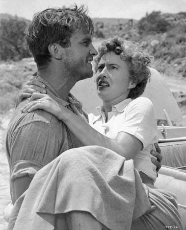 Medium shot of Ralph Meeker as Lawson carrying Barbara Stanwyck as Helen Stilwin.