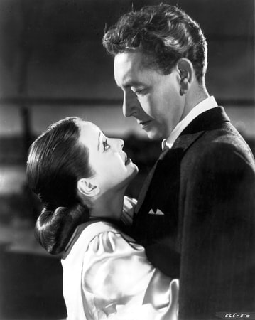 Medium profile shot of Bette Davis as Christine Radcliffe embracing Paul Henreid as Karel Novak.