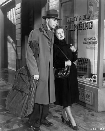 Full shot of Paul Henreid as Karel Novak, wearing hat, and Bette Davis as Christine Radcliffe, walking down sidewalk.