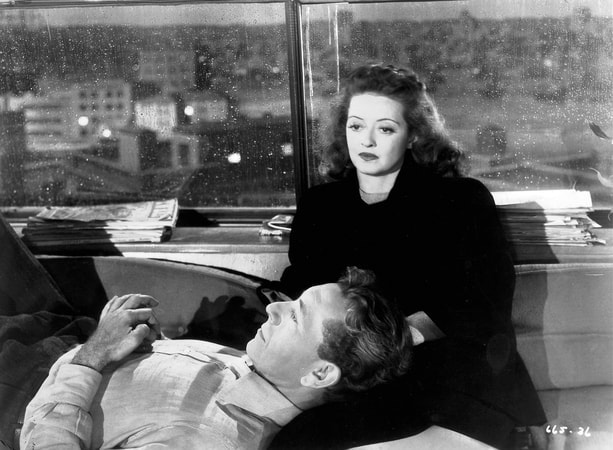 Medium shot of Paul Henreid as Karel Novak laying head on lap of Bette Davis as Christine Radcliffe.