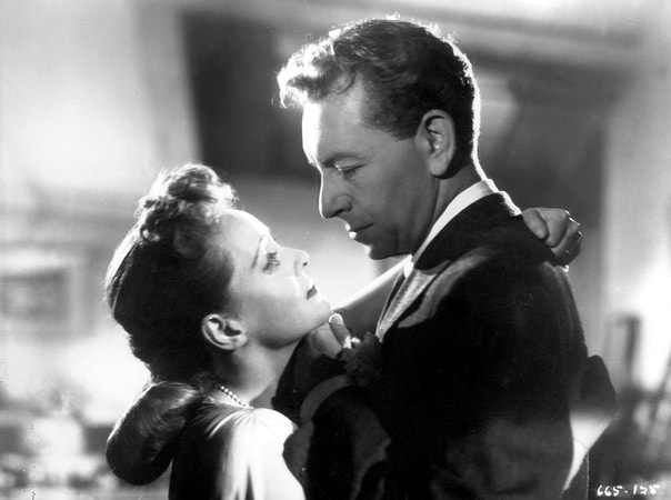 Medium profile shot of Bette Davis as Christine Radcliffe and Paul Henreid as Karel Novak.
